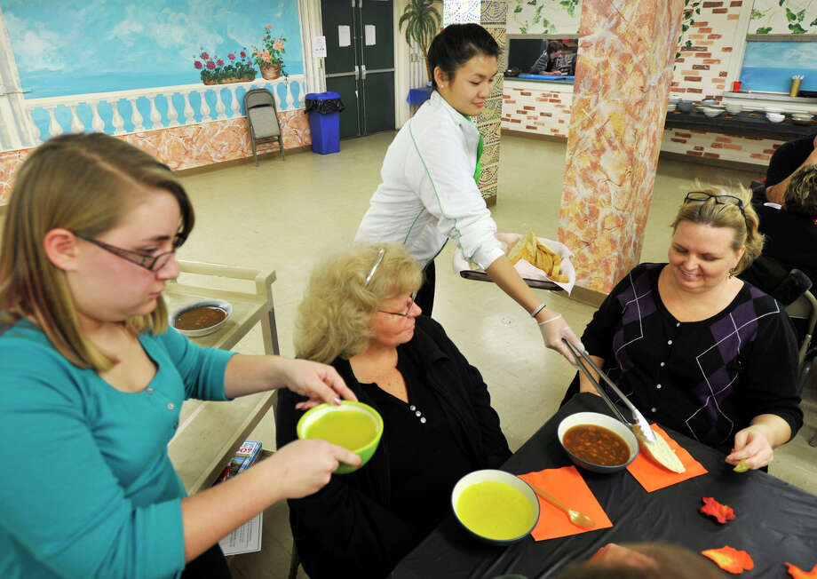 Elizabeth Belote, left, hands out soup and Daniella Wong hands out bread as Judith Hibbard, seated left, and her daughter, Kelli Hibbard, wait to eat during the ProAccess the Bethel Teen Center's Souper Soup Day at the Hurgin Municipal Center in Bethel on Wednesday, Nov. 14, 2012. Photo: Jason Rearick / The News-Times
