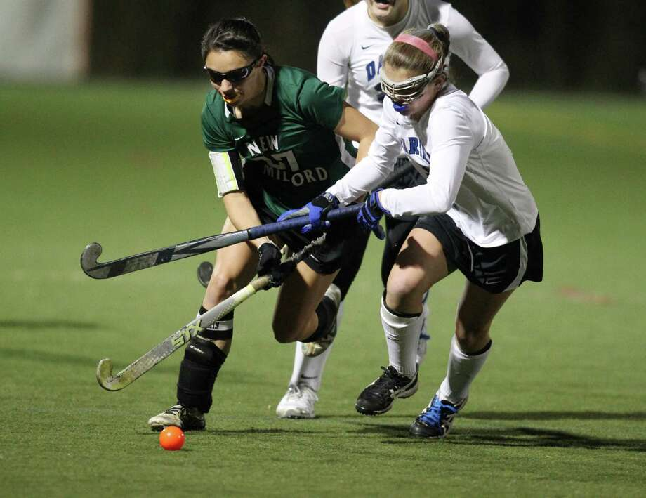 New  Milford player Vienna Pallisco battles for possession of a loose ball with Darien's Georgia Cassidy during semifinal state field hockey in Weston on Wednesday night. The two teams played a scoreless first half. Photo: J. Gregory Raymond / Stamford Advocate Freelance;  © J. Gregory Raymond