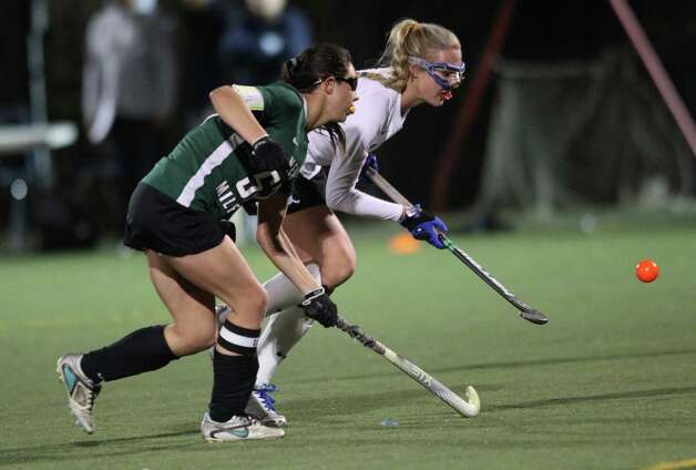New  Milford player Vienna Pallisco battles for possession of a loose ball with Darien's Holis Perticone Cassidy during first half semifinal state field hockey in Weston on Wednesday night. The two teams played a scoreless first half. Photo: J. Gregory Raymond / Stamford Advocate Freelance;  © J. Gregory Raymond