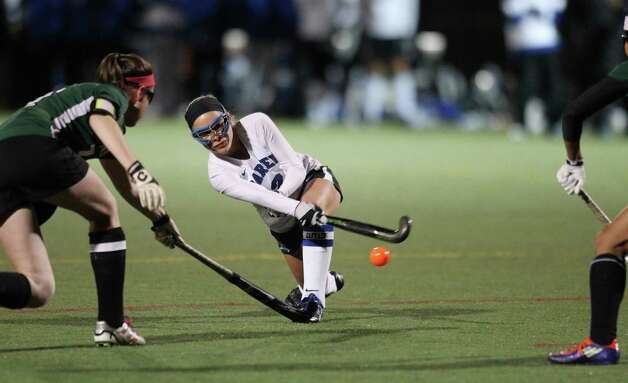Kat Huber of Darien passes the ball to an open teammate despite the defensive efforts of two New Milford defenders during their state field hockey match in Weston on Wednesday evening. The two squads played a scoreless first half. Photo: J. Gregory Raymond / Stamford Advocate Freelance;  © J. Gregory Raymond