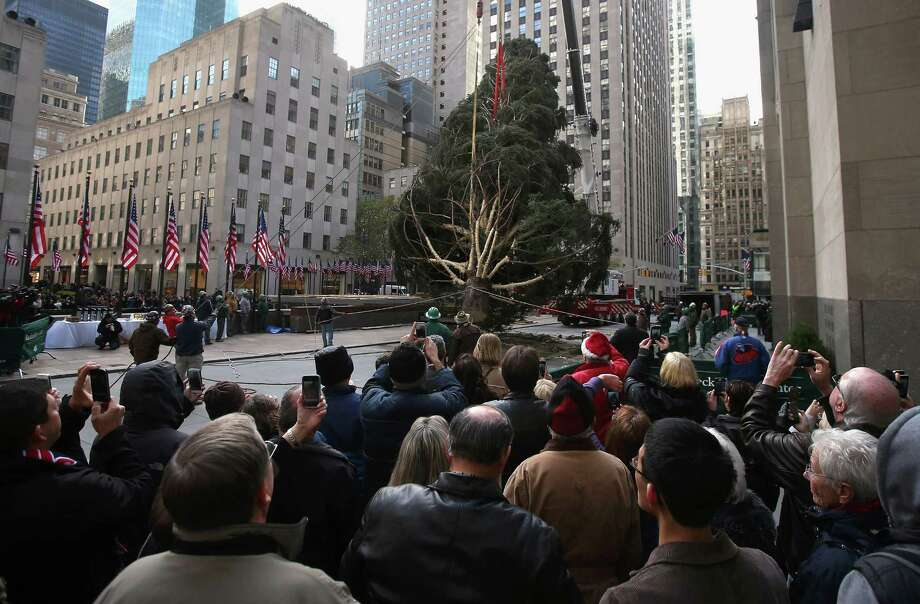 People watch as the Rockefeller Center Christmas tree is raised into position on November 14, 2012 in New York City. The tree, an 80-year old Norway Spruce, was donated by Joe Balku of Flanders, New Jersey. It weighs approximately 10 tons, measures 80 feet tall and is 50 feet in diameter. The official tree-lighting ceremony will be Wednesday, November 28. Photo: John Moore, Getty Images / 2012 Getty Images