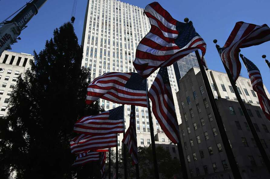Flags wave as the Rockefeller Center Christmas tree is raised into position on November 14, 2012 in
