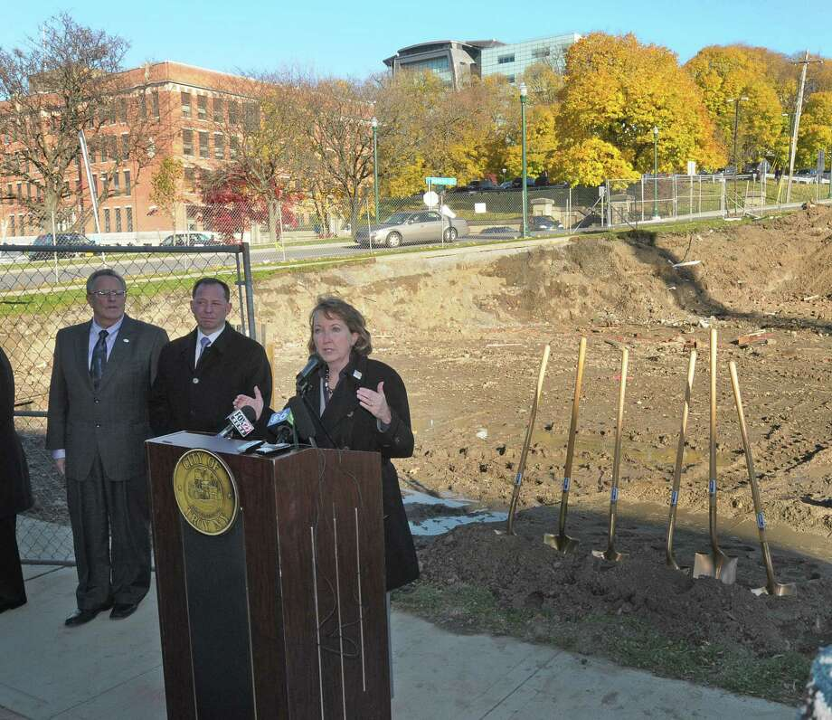 Rensselaer County Executive Kathy Jimino, foreground, addresses those gathered during a groundbreaking for City Station East on Wednesday, Nov. 14, 2012 in Troy, NY.  Also pictured is Troy Mayor Lou Rosamilia, background left, and Michael Uccellini, President and CEO, The United Group.   During the groundbreaking ceremony it was also announced that a section of Sixth Ave. will be renamed Walter Uccellini Ave. after a longtime Troy businessman and developer who passed away.  Michael Uccellini is the son of  Walter Uccellini. (Paul Buckowski / Times Union) Photo: Paul Buckowski  / 00020121A