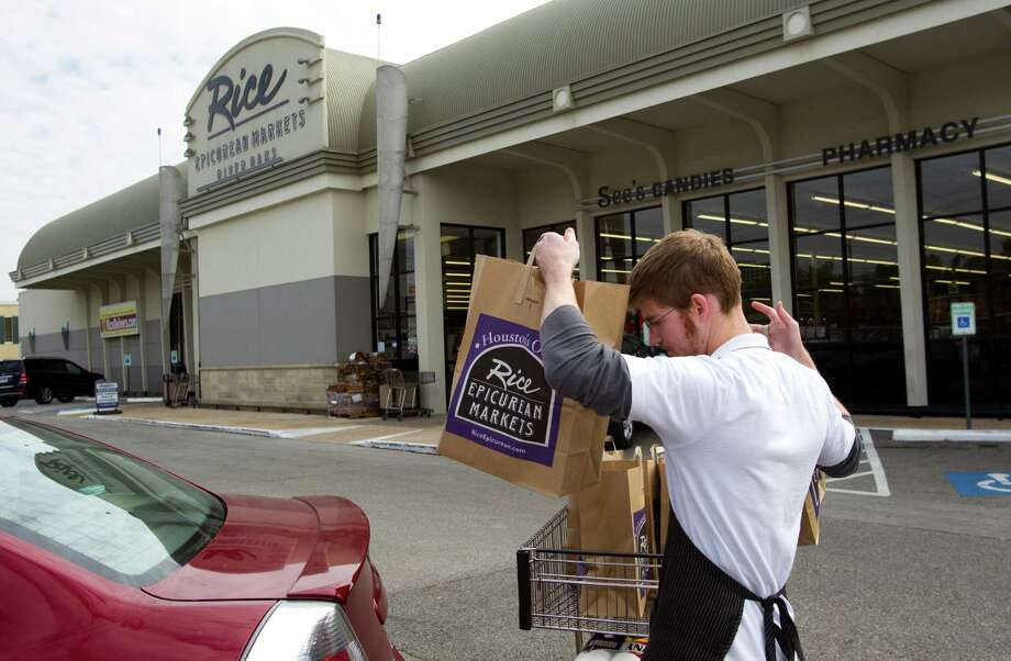 Tyler Brantley carries bags for a customer at Rice Epicurean Markets in River Oaks on Wednesday, Nov. 14, 2012, in Houston. Photo: Brett Coomer, Houston Chronicle / © 2012 Houston Chronicle