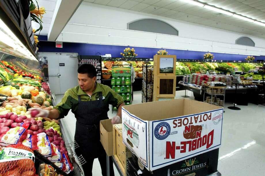 Produce clerk Marcelo Lopez stocks potatoes at Rice Epicurean Markets in River Oaks on Wednesday, Nov. 14, 2012, in Houston. T Photo: Brett Coomer, Houston Chronicle / © 2012 Houston Chronicle