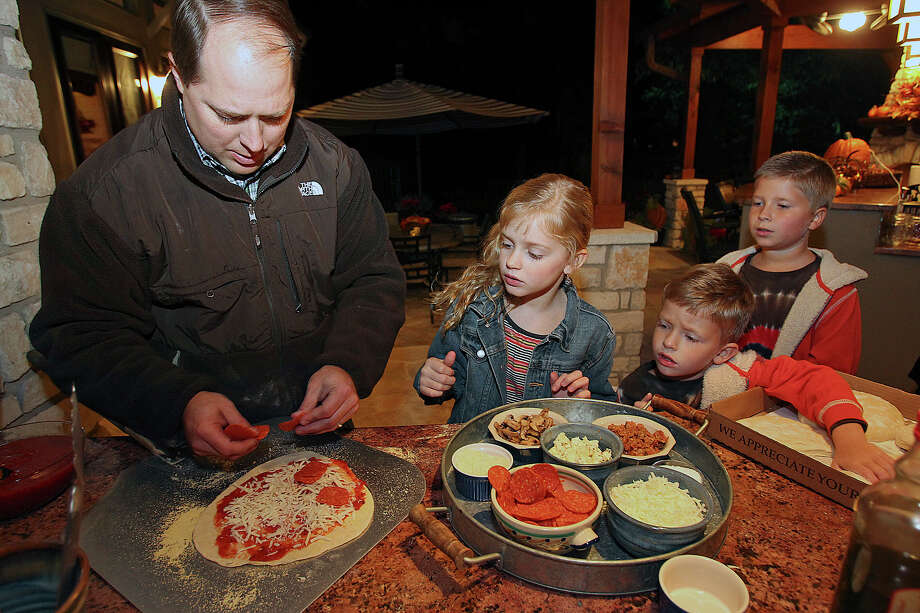 Chris gets the kids (from left) McKenzie, Christian and Hayden in the work flow as the Pheiffer family cooks in their outdoor kitchen on November 13, 2012. Photo: Tom Reel, San Antonio Express-News / ©2012 San Antono Express-News