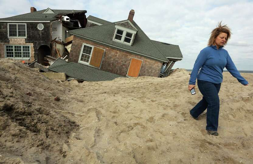 Lisa Baney walks back toward her family's home after taking a photo of a neighbor's destroyed home o