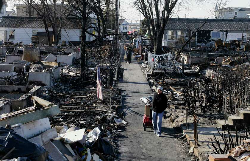 Louise McCarthy carts belongings from her flood-damaged home as she passes the charred ruins of othe