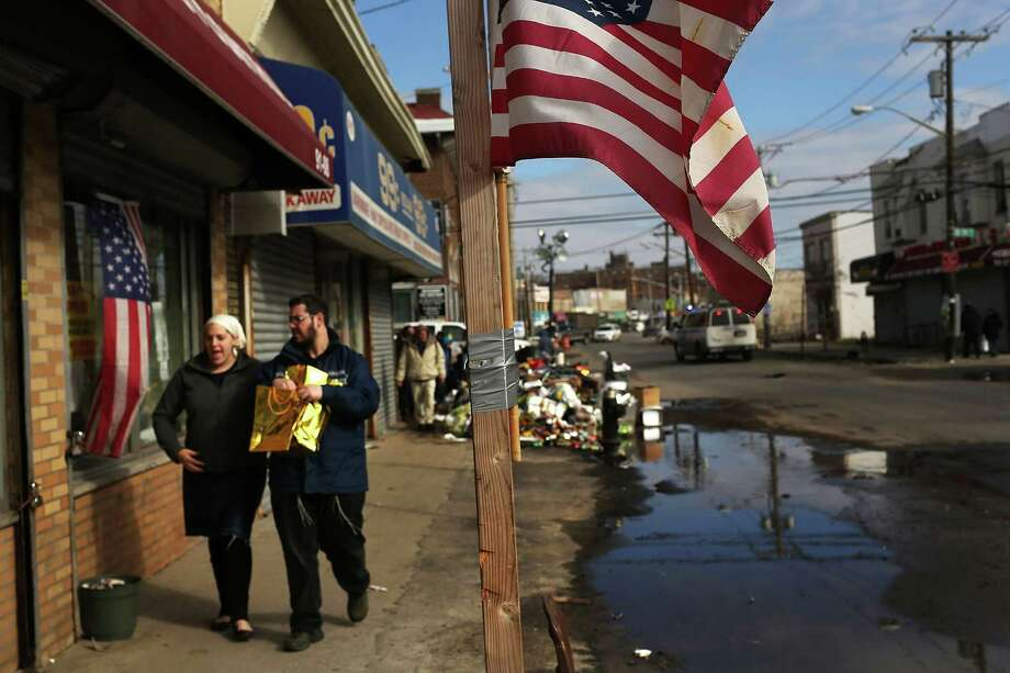 NEW YORK, NY - NOVEMBER 14: A couple walks with items discarded from a flooded store in the heavily damaged Rockaway neighborhood where a large section of the iconic boardwalk was washed away on November 14, 2012 in the Queens borough of New York City. Two weeks after Superstorm Sandy slammed into parts of New York and New Jersey, thousands are still without power and heat. Photo: Spencer Platt, Getty Images / 2012 Getty Images