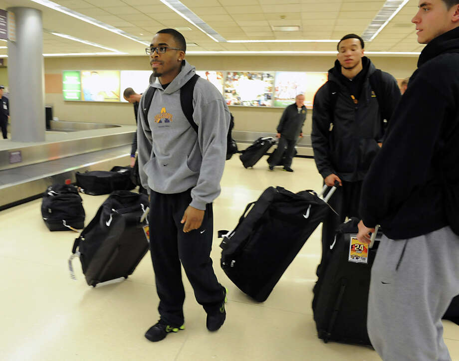 The UAlbany men's basketball team, which upset Washington on Tuesday night, returns  from Seattle and waits for their luggage at the Albany International Airport on Wednesday, Nov. 14, 2012 in Albany, N.Y.  Mike Black, left, scored the winning basket. (Lori Van Buren / Times Union) Photo: Lori Van Buren