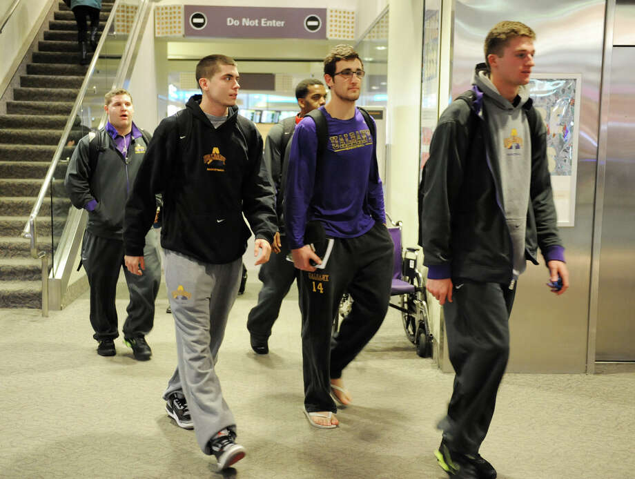 The UAlbany men's basketball team, which upset Washington on Tuesday night, returns  from Seattle at the Albany International Airport on Wednesday, Nov. 14, 2012 in Albany, N.Y.  (Lori Van Buren / Times Union) Photo: Lori Van Buren