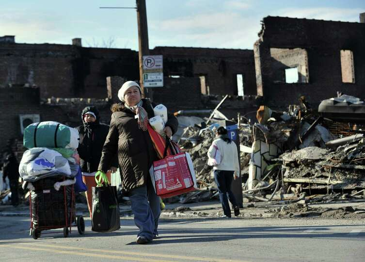 After getting household supplies from a nearby distribution center, people walk home past burned out