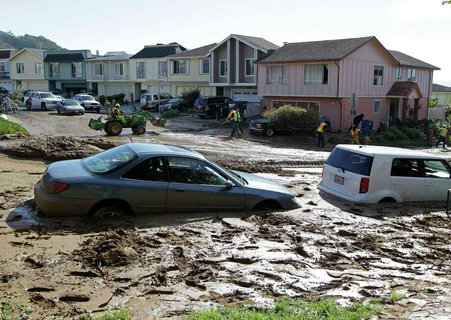 Cars sit buried in mud as crews continue clean up efforts after a broken water main sent water down a hillside in Daly City, Calif., Tuesday, Nov. 13, 2012. Residents in the Hillside Park neighborhood woke up to flooded streets and vehicles stuck in mud after a broken water main sent 45,000 gallons of water spewing down a grassy hillside. (AP Photo/Eric Risberg) Photo: Eric Risberg