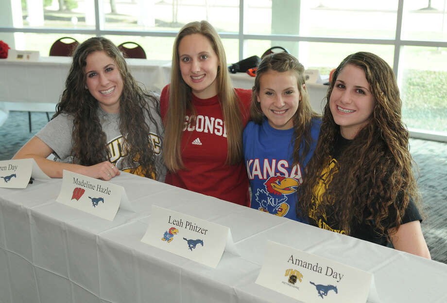 The girls swimming team at Kingwood showed its strength with four signees, including twins Lauren, left, and Amanda Day, who will attend Maryland-Baltimore County; Madeline Hazle, second from left, who is headed to Wisconsin; and Leah Pfitzer, who will attend Kansas. Photo: Jerry Baker, Freelance
