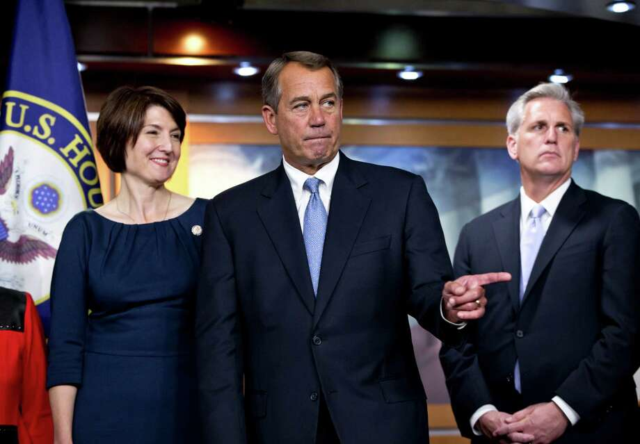 Speaker of the House John Boehner, R-Ohio, center, speaks to reporters after the House Republicans voted for their leadership for the next session of Congress, at the Capitol in Washington, Wednesday, Nov. 14, 2012. House Republicans elevated Rep. Cathy McMorris Rodgers, R-Wash., left, to lead the Republican Conference, with House Majority Whip Kevin McCarthy, R-Calif., right, returning in his role. House Majority Leader Eric Cantor, R-Va., and Boehner were both reelected to their leadership posts.  (AP Photo/J. Scott Applewhite) Photo: J. Scott Applewhite
