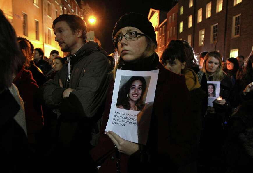 Protestors hold pictures of Indian Savita Halappanavar, who was allegedly refused a pregnancy termin