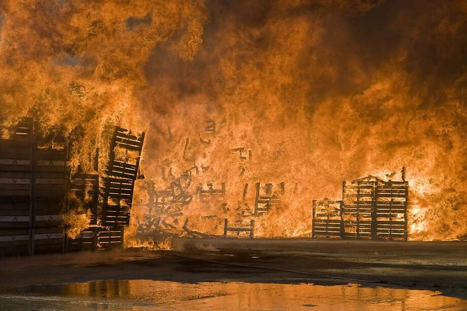 "Fruit bins burn at a packing store on November 14, 2012 in Wolesley, about 120Km North of Cape Town, South Africa. The fire, which burnt more than 15000 wooden bins is thought to be connected to the farmworkers strike. South African police on Wednesday said one person was killed and five others injured as protests by farm workers demanding higher pay descended into violence, prompting calls for the military to be deployed. A week-long protest by farm workers spilled over into bloodshed with chilling echoes of recent mining unrest that has claimed more than 50 lives. ""We can confirm the death of a 28-year-old man in Wolseley and five others wounded,"" Lybey Swartz of the Western Cape police told AFP. Photo: Rodger Bosch, AFP/Getty Images"