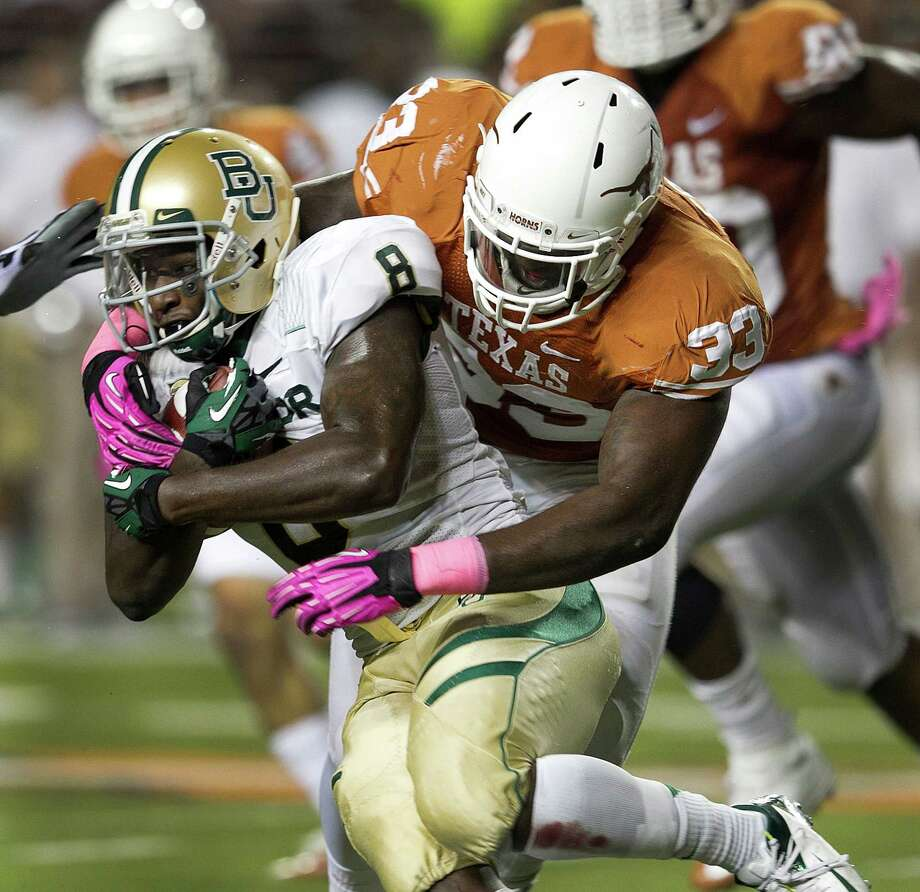 Texas linebacker Steve Edmond takes down Baylor running back Glasco Martin for one of his team-high 10 tackles during their Oct. 20 game in Austin. Photo: Deborah Cannon, MBR / Austin American-Statesman