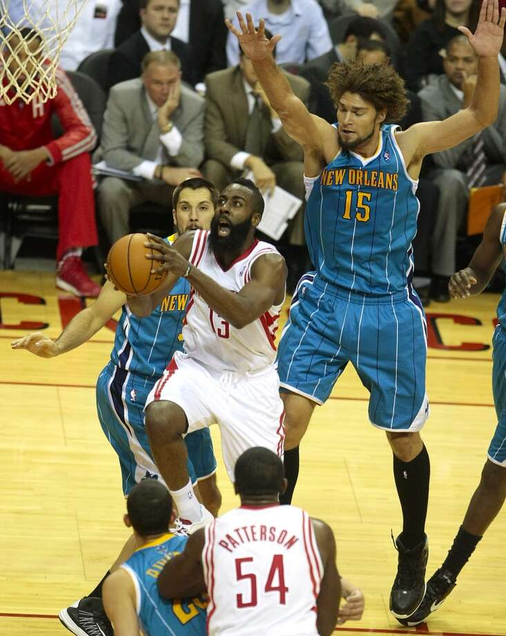 Rockets guard James Harden (13) cuts to the basket while Hornets center Robin Lopez (15) attempts to defend. (Billy Smith II / Houston Chronicle)