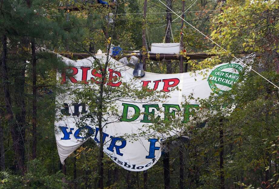 A sign hung by members of the Tar Sands Blockade hangs above a site where TransCanada is working to finish their Keystone XL project in Wood County Wednesday, Oct. 24, 2012, in Winnsboro, Texas. The group possesses an aggressive effort to stop work on the southern portion of TransCanada's Keystone XL pipeline. The following essay focuses on a community in East, Texas affected by the $2.3 billion Oklahoma-Texas leg of a line eventually planned to link Canada with the Gulf Coast. (Houston Chronicle)