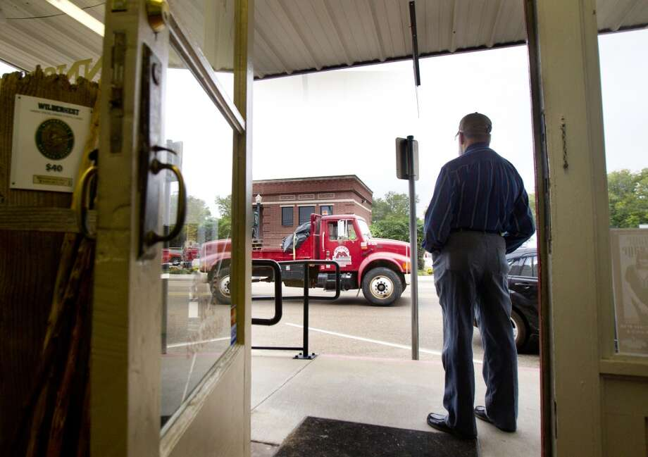 "Conrad Wolfman watches from his storefront as a truck that hauls equipment for TransCanada's Keystone XL project drives through downtown Winnsboro, Thursday, Oct. 25, 2012, in Wood County. While he has read material from those opposed to and supportive of the pipeline, many of his questions about how a spill would be cleaned up, or the type of oil that would move through Keystone XL, have not been answered by TransCanada or government officials, he said. ""We don't know any of that stuff, and I don't know if it's because they don't know or they don't want us to know,"" Wolfman said. (Houston Chronicle)"