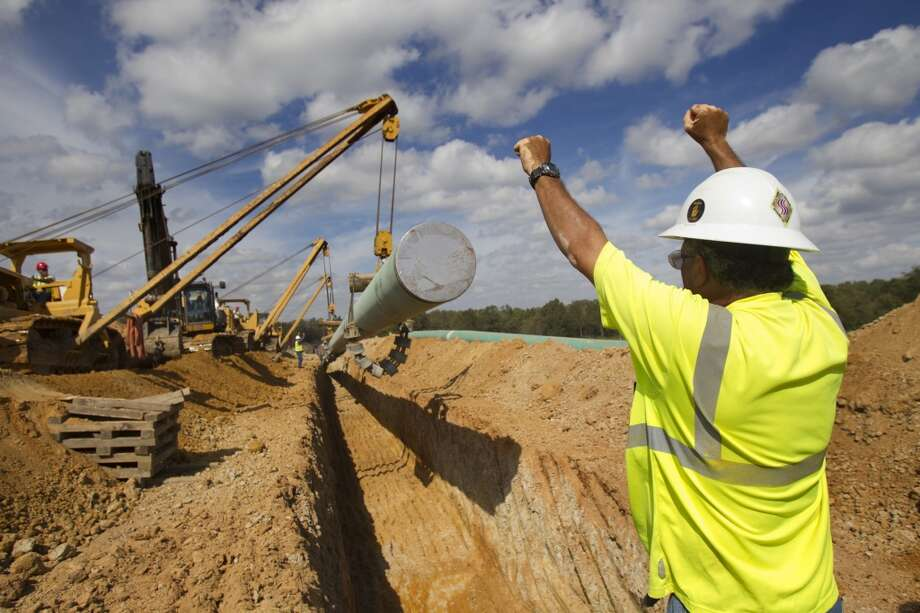A crewmen directs a capped pipe as the end of the segment is lowered into the ground ending a leg of TransCanada's Keystone XL project in Wood County, Wednesday, Oct. 24, 2012, in Winnsboro, Texas. Although work has been interrupted several times by protesters in East Texas, the Canadian pipeline company has soldiered on. (Houston Chronicle)
