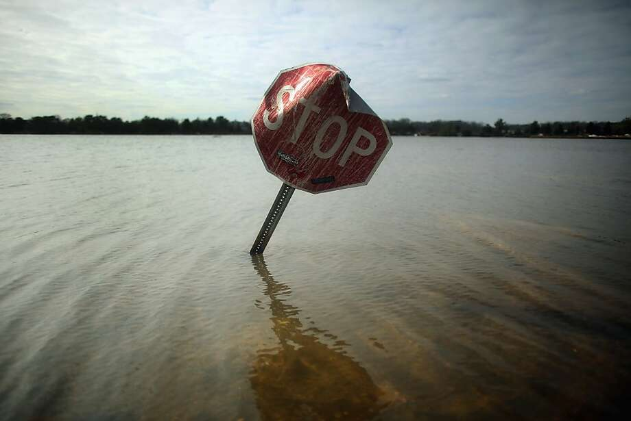 A sign warns nonexistent traffic to stop in a still-flooded 