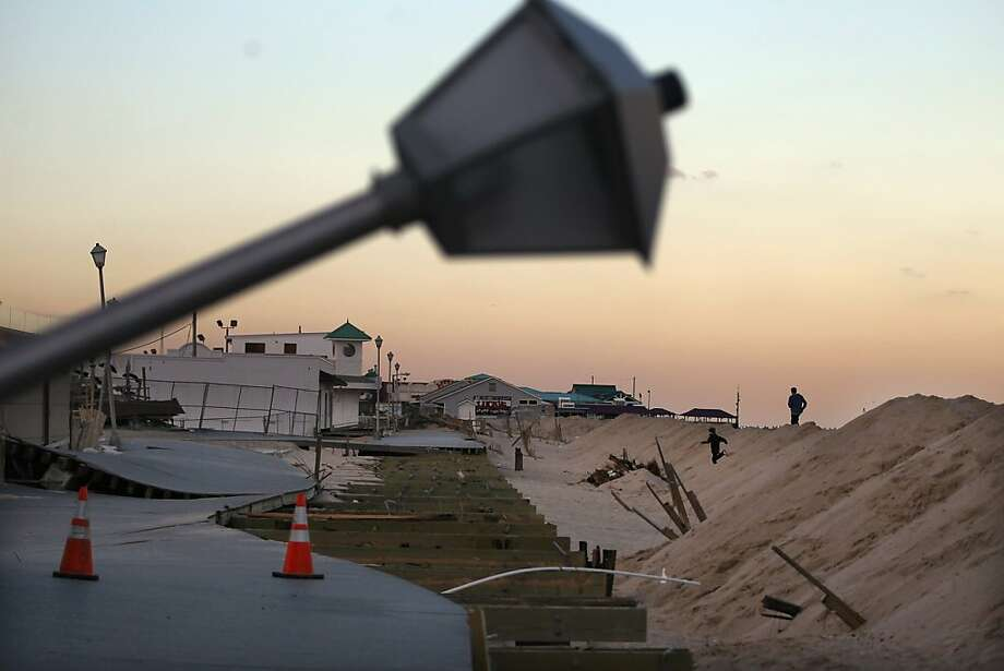 Boys run over piles of sand intended to prevent possible a future storm surge in front of a damaged section of boardwalk on November 14, 2012 in Point Pleasant Beach, New Jersey. Many residents of the seaside town remain without power following Superstorm Sandy. Photo: Mario Tama, Getty Images
