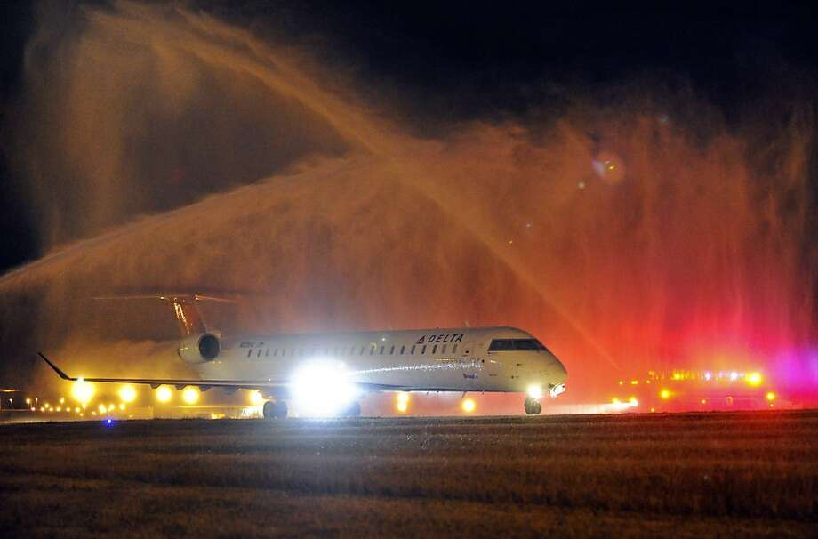 An airplane carrying Korean War Veterans returning from trip to South Korea is welcomed with a water cannon salute at Huntsville International Airport in Huntsville, Ala., on Wednesday, Nov. 14, 2012. Photo: Bob Gathany, Associated Press