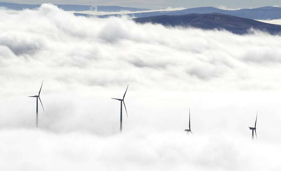 Wind turbines at the Vantage Wind Farm stand above the clouds Nov. 14, 2012 at Vantage, Wash.. Clouds lay low in the valleys of central Washington but more sun is forecast for the area on Thursday, Nov. 15. Photo: Gordon King, Associated Press