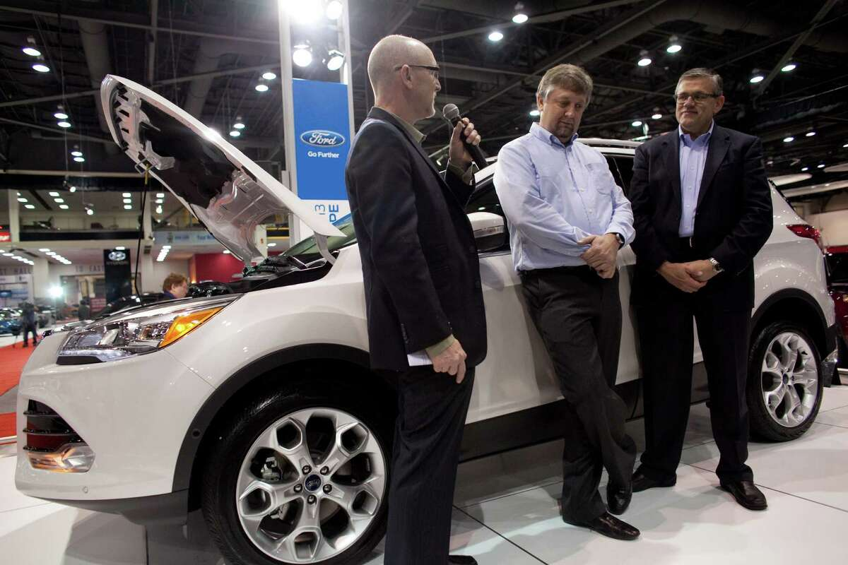 From left, automotive journalist Doug Newcomb, Walter Sullivan, a senior program manager with Microsoft, and Jim Buczkowski, a Ford director of research and innovation, speak about their new lineup of cars on Wednesday, November 14, 2012 during the opening day of the Seattle Auto Show at CenturyLink Field Events Center.