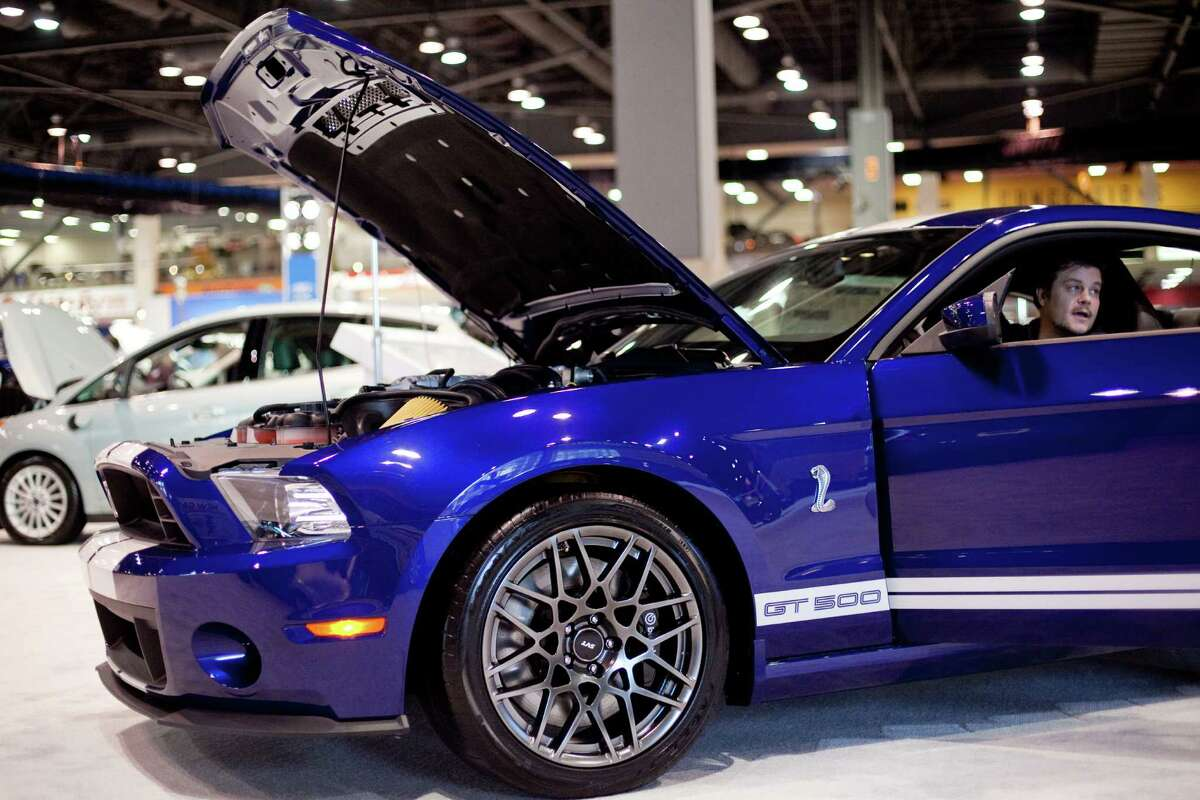 A visitor sits in a Ford Mustang on Wednesday, November 14, 2012 during the opening day of the Seattle Auto Show at CenturyLink Field Events Center.