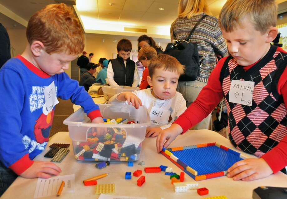 EJ Verhoff,3, of Albany ,left, and his cousins Matt Bishop, 3, and Michael Bishop,5, at right, of East Greenbush compete in the LEGO�® Building Challenge at the 2011 Gift Fair & Family Festival at the Albany Institute of History & Art Friday Nov. 25, 2011.    (John Carl D'Annibale / Times Union) (Albany Times Union)