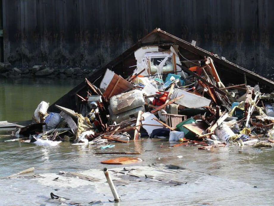The havoc caused by Hurricane Sandy in Fairfield -- here, parts of a storm-destroyed house float in Pine Creek -- forced the cancellation of six days of classes by Fairfield's public schools. Photo: File Photo / Fairfield Citizen