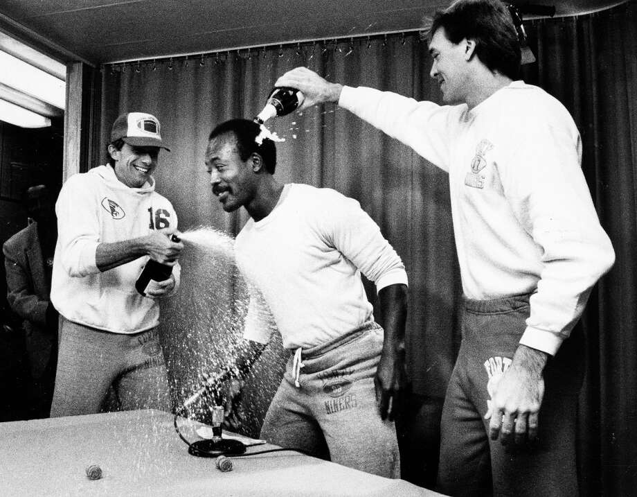 Dec. 20, 1984: That's the great Freddie Solomon, getting a champagne shower from Montana and Clark. He seems cool with it, but I'm guessing they destroyed that microphone. RIP Freddie Solomon.  (Jerry Telfer / The Chronicle) Photo: Jerry Telfer, San Francisco Chronicle / ONLINE_YES