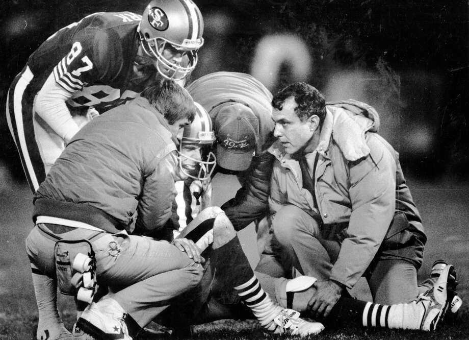 "Dec. 14, 1987: Clark checks in on an injured Joe Montana against the Bears. I can almost picture Montana yelling ""Where's Dwight!"" ... ""I'm here."" Montana was hurt early in the game. Steve Young passed for four touchdowns and the 49ers won 41-0. Photo: Fred Larson, The Chronicle / ONLINE_YES"
