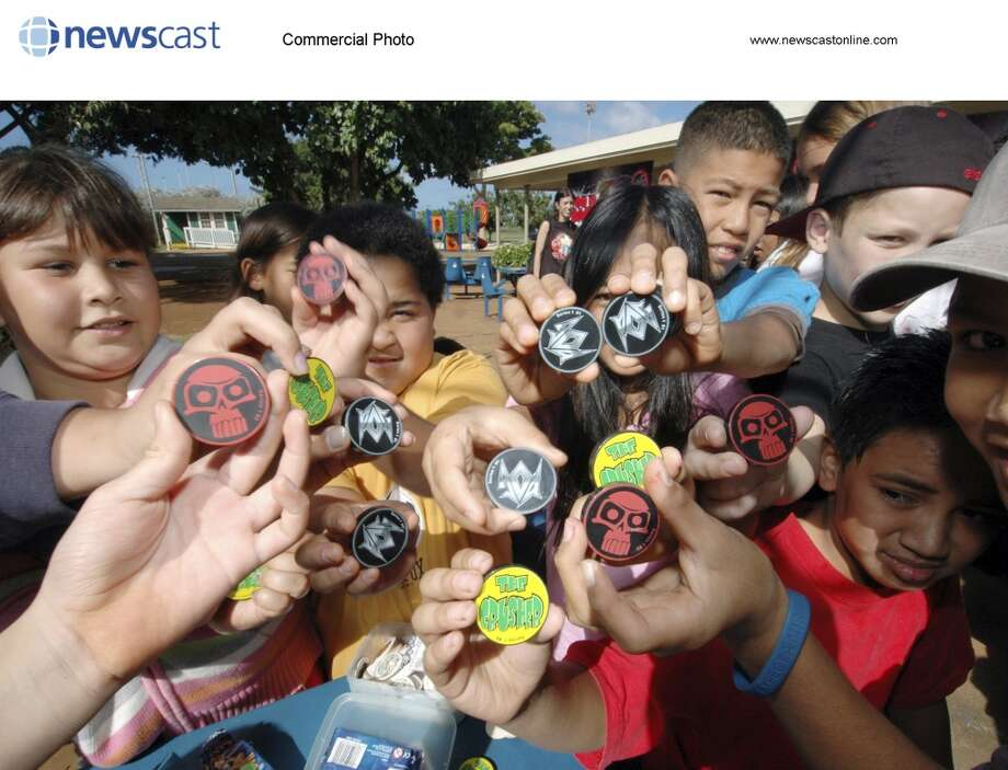 Kids at the Waialua Elementary School in Hawaii show off their new POGs on Tuesday, December 13, 2005.  Funrise Toy Corp announced the re-introduction of a classic Hawaiian game - POG, the collectible game of flipping milk-caps.  Students at the school, where the POG craze began in the early 1990's, were the first to test out the new POG a full two months before the POG will be released worldwide.  (Ronen Zilberman/newscast) (NEWSCAST)