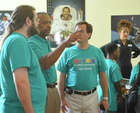 "Astronaut  Bernard Harris, middle, talks with physics major Bryan Neal, left, and Associate Professor of Physics Cristian Bahrim, right, as everyone waited for the results of theimpact test to be tabulated. The 6th-8th grade campers  participated in a ""space suit challenge"" at Lamar University as part of the ExxonMobil Bernard Harris Summer Science Camp, where they designed and created a space suit swatch capable of absorbing the impact of space debris. Dr. Bernard Harris' summer science camp is the largest of its kind in the nation and offers an all-expenses-paid, two-week experience for the selected local students. The designing and testing was held at the Dishman Art Museum on the Lamar Campus.  Dave Ryan/The Enterprise Photo: Dave Ryan"