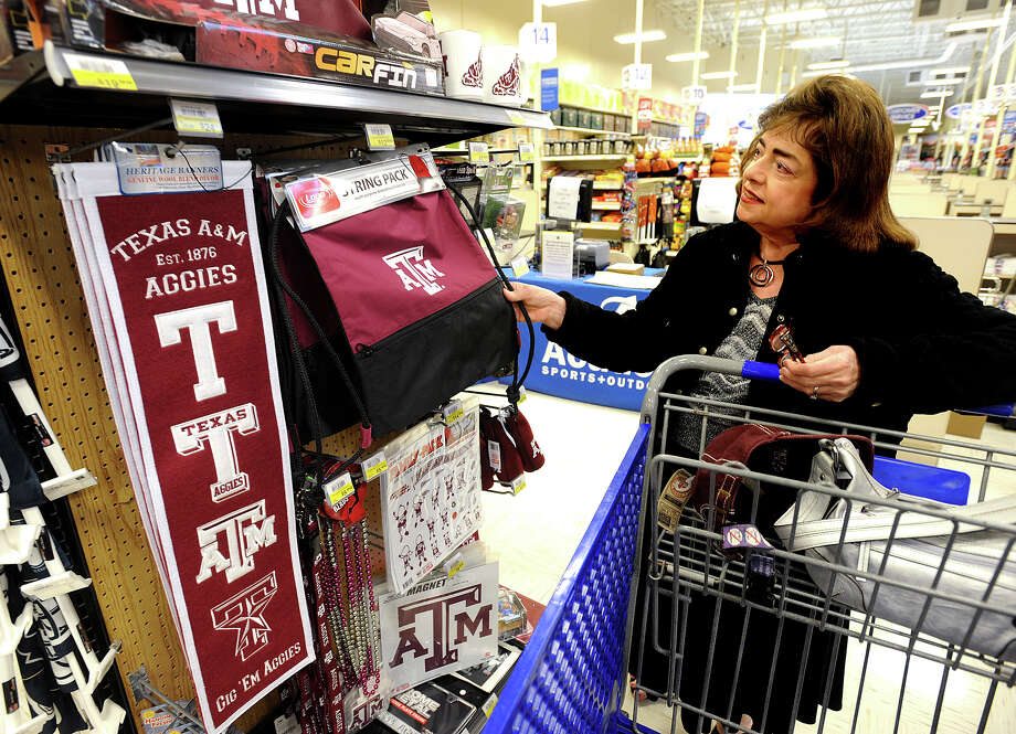 With the Aggie's recent win over Alabama, the school's merchandise has become a hot ticket item. Gail Miranda looks over Texas A&M apparel for her grandson Christopher Gaudio, 8, while at Academy in Beaumont on Wednesday. Miranda said Gaudio believes the Aggies should be ranked number one after beating top ranked school.  Photo taken Wednesday, November 14, 2012 Guiseppe Barranco/The Enterprise Photo: Guiseppe Barranco, STAFF PHOTOGRAPHER / The Beaumont Enterprise
