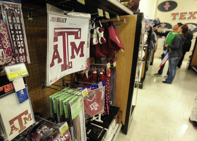With the Aggie's recent win over Alabama, the school's merchandise has become a hot ticket item. Francisco Lopez and Erica Lopez purchase football merchandise at Academy in Beaumont on Wednesday.  Photo taken Wednesday, November 14, 2012 Guiseppe Barranco/The Enterprise Photo: Guiseppe Barranco, STAFF PHOTOGRAPHER / The Beaumont Enterprise