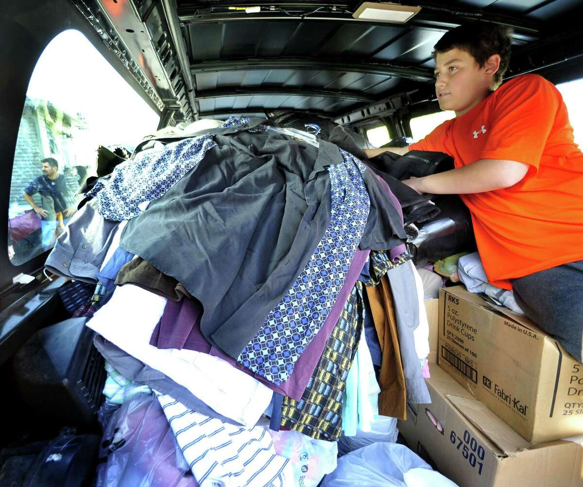 Ryan Solimine, 13, squeezes donated clothes into an overfull van during the DPZ Group event to benefit Superstorm Sandy victims in Danbury Sunday, Nov. 11, 2012.
