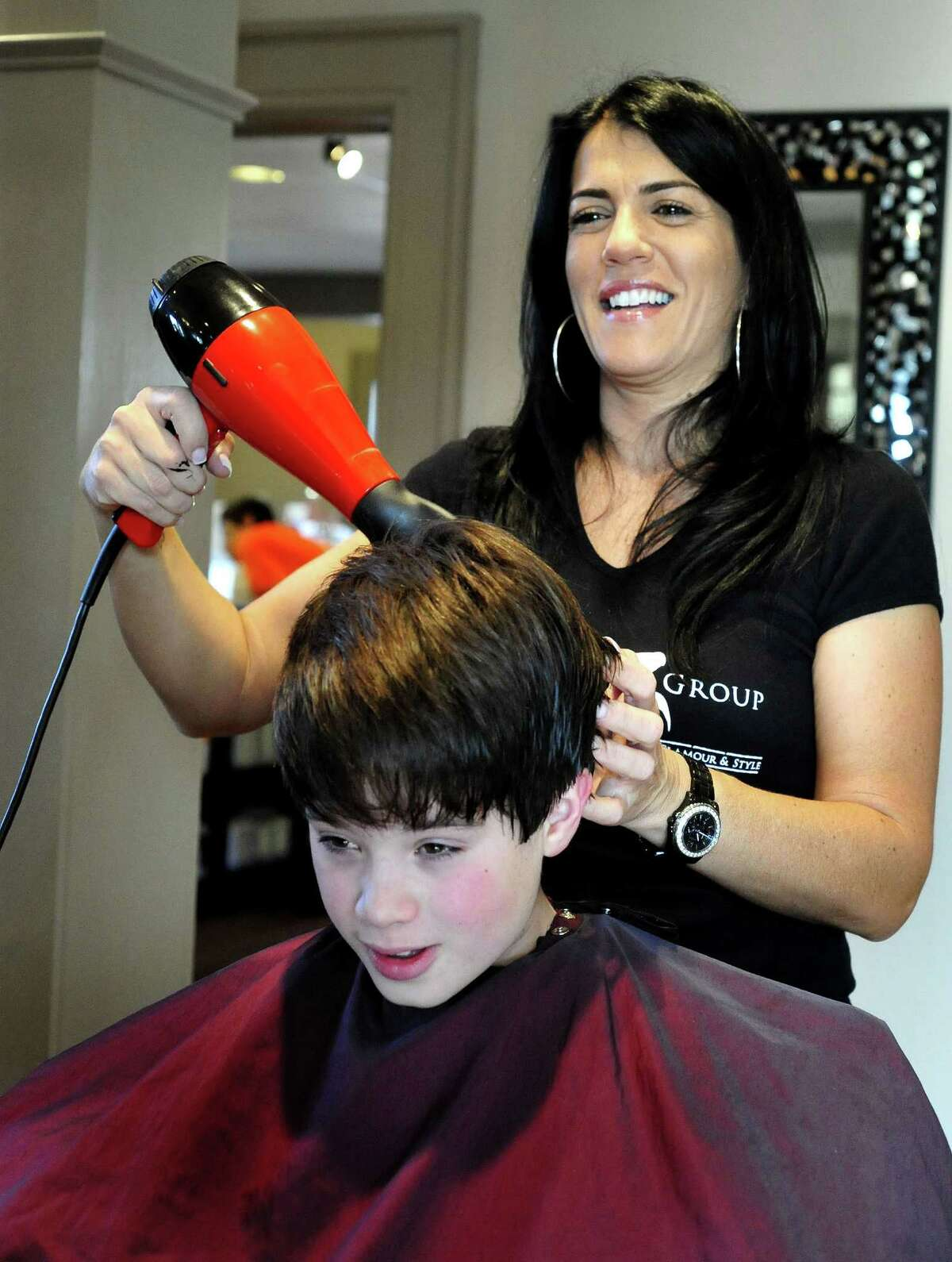 Aaron Gayle, 8, has his hair blown out by Sandy Russo during the DPZ Group event to benefit Superstorm Sandy victims in Danbury Sunday, Nov. 11, 2012.