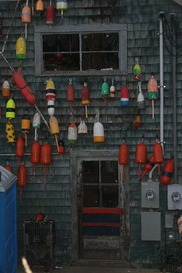Lobster floats hang on a wall in Bass Harbor, Maine. They're colorful and interesting to look at if you're not trying to navigate a boat through a large field of lobster traps with floats bobbing on the water's surface.