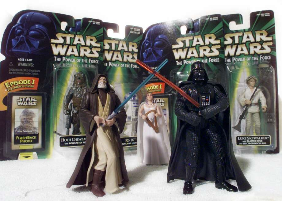 "FILE - ""Star Wars"" action figures Darth Vader, right, and Ben (Obi-Wan) Kenobi, left, are displayed in this April 7, 1999 file photo, with Princess Leia Organa in her ceremonial dress in front of other packaged characters from the new film. The National Toy Hall of Fame announces its class of 2012 Thursday Nov. 15, 2012. Two toys will be inducted into the Rochester hall from among 12 nominees. (AP Photo/ Victoria Arocho, File) Photo: VICTORIA AROCHO"