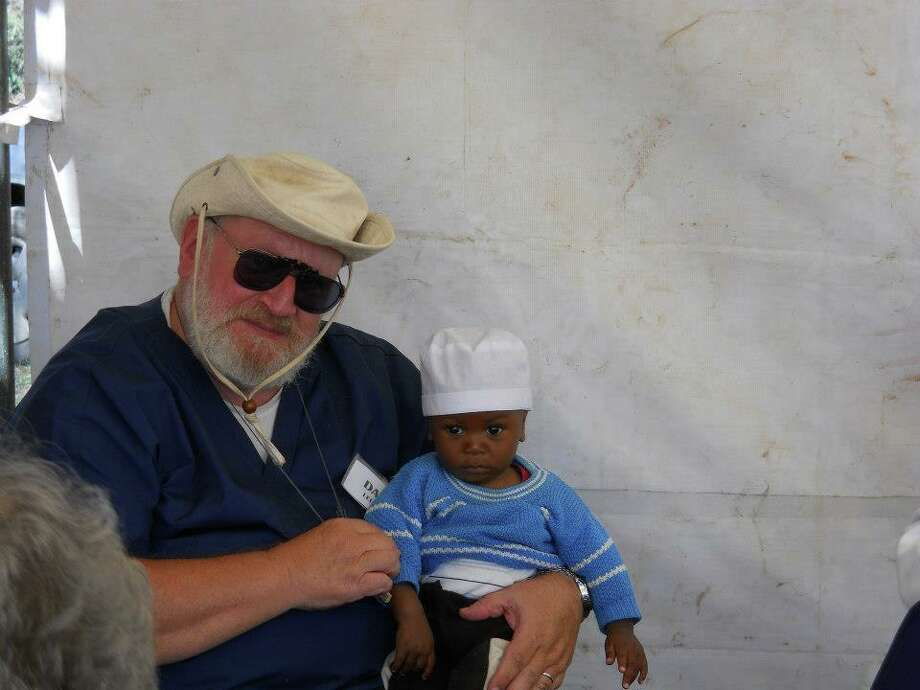 Rev. Dale Leland, of Sealy, TX, holds a young child waiting for his mother (Photo: Pam Epperly)