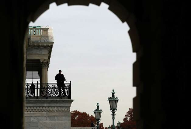 WASHINGTON, DC - NOVEMBER 15: A Capitol Police Officer stands guard as Congressional freshmen of the 113th Congress pose for a class picture on the steps of the U.S. Capitol on November 15, 2012 in Washington DC. The freshmen have arrived on Capitol Hill for orientation this week. The 109th Congress will officially begin in January, next year. (Photo by Mark Wilson/Getty Images) Photo: Mark Wilson, Getty Images / 2012 Getty Images