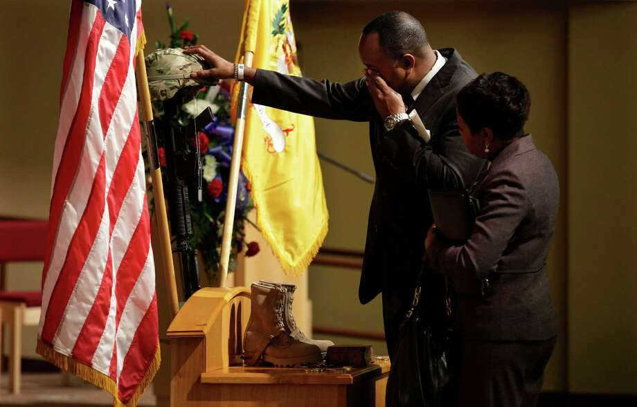 Cedric Gordon, left,, rubs the surname embroidered on the helmet of his daughter, U.S. Army Spc. Brittany Gordon, Wednesday, Nov. 14, 2012, following a memorial service for her at Joint Base Lewis McChord, Wash. At right is Cedric Gordon's fiancee, Jean Teal. Brittany Gordon was killed in Afghanistan on Oct. 13, 2012, when officials say an Afghan intelligence officer detonated the suicide vest he was wearing while Gordon and other soldiers were delivering furniture to an intelligence office. Cedric Gordon is the assistant Chief of Police in St. Petersburg, Fla. Photo: Ted S. Warren / Associated Press