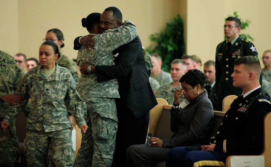 A solider hugs Cedric Gordon, the father of U.S. Army Spc. Brittany Gordon, Wednesday, Nov. 14, 2012, following a memorial service for Brittany Gordon at Joint Base Lewis McChord, Wash. At third from right is Cedric Gordon's fiancee, Jean Teal. Brittany Gordon was killed in Afghanistan on Oct. 13, 2012, when officials say an Afghan intelligence officer detonated the suicide vest he was wearing while Gordon and other soldiers were delivering furniture to an intelligence office. Cedric Gordon is the assistant Chief of Police in St. Petersburg, Fla. Photo: Ted S. Warren / Associated Press