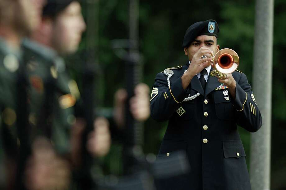 "A member of the Army I Corps band plays ""Taps"" at a memorial service for U.S. Army Spc. Brittany Gordon, Wednesday, Nov. 14, 2012, at Joint Base Lewis McChord, Wash. Gordon was killed in Afghanistan on Oct. 13, 2012, when officials say an Afghan intelligence officer detonated the suicide vest he was wearing while Gordon and other soldiers were delivering furniture to an intelligence office. Photo: Ted S. Warren / Associated Press"