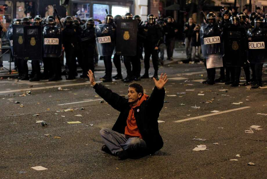 A protestor sits in front of the riot police riot to stop the clashes during a general strike in Madrid, Spain, Wednesday, Nov. 14, 2012. Spain's main trade unions stage a general strike, coinciding with similar work stoppages in Portugal and Greece, to protest government-imposed austerity measures and labor reforms. The strike is the second in Spain this year. (AP Photo/Andres Kudacki) Photo: Andres Kudacki